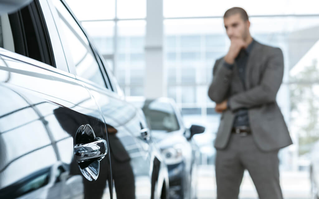 man thinking about buying a car